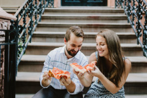 couple eating pizza on a brownstone