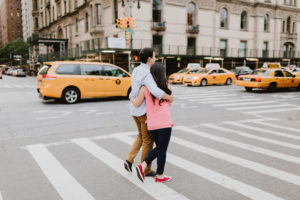 NYC couple holding hands next to a cab